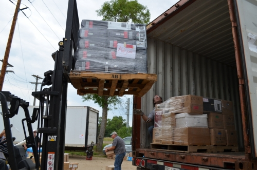 Loading the shipping container with donated computers and educational materials, for transport to Ghana.