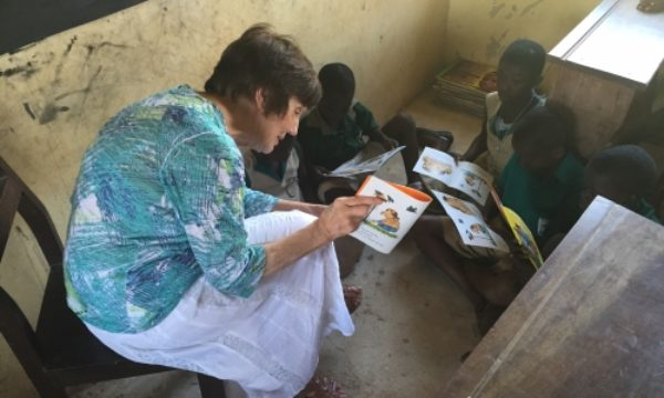 Joan reading to school children in Ghana