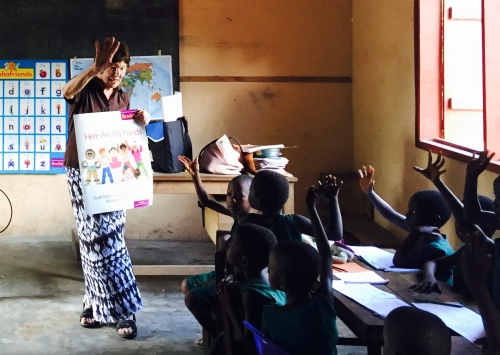 Joan teaching students, using newly donated educational materials.