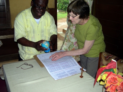 Joan and Monsignor Francis Tawiah discuss school needs in Takoradi.